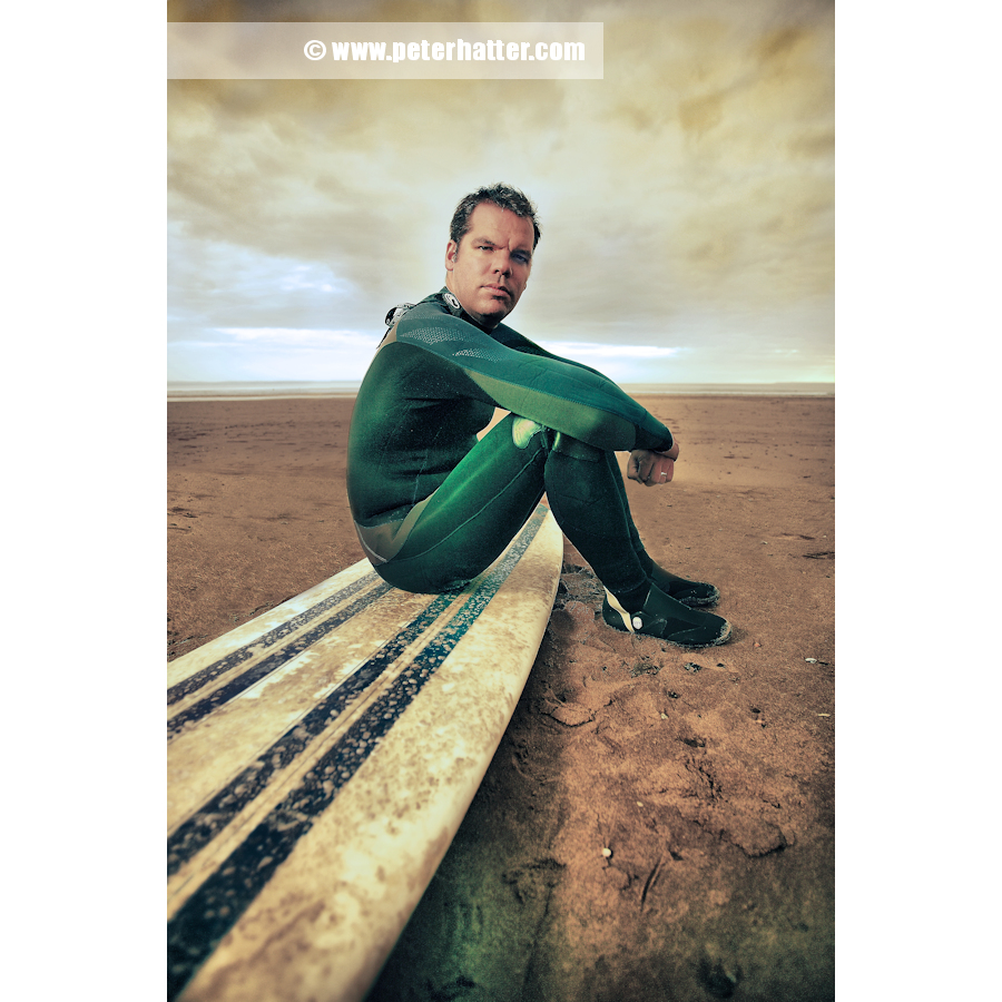 Portrait of surfer sitting on his board